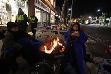 (AP Photo/Ringo H.W. Chiu). Rose Parade spectators keep warm around a fire while waiting the start of the 126th Rose Parade in Pasadena, Calif., Thursday, Jan. 1, 2015.