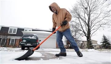 (AP Photo/Daily Herald, Mark Welsh). Sal Evola of Arlington Heights dons his winter coat and snow shovel and pushes the wet rainy mess away from his driveway and sidewalks around his house as winter decided to show up after all on Saturday, Jan. 3, 2015