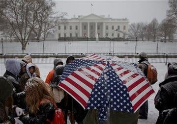 (AP Photo/Carolyn Kaster). A light snow falls on a tour group outside the White House in Washington, Tuesday, Jan. 6, 2015, as temperatures hover around freezing.