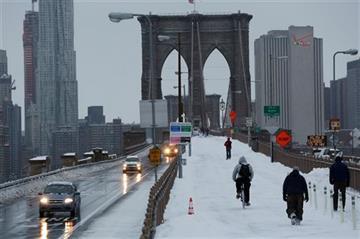 (AP Photo/Mark Lennihan). Pedestrians and cars cross the Brooklyn Bridge, Tuesday, Jan. 27, 2015 in New York.