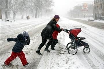 (AP Photo/Chicago Tribune, Michael Tercha). Christie Capshaw runs across North Avenue at California Avenue with her son James, 5, neighbor Sebastian, 4, and son William, 1, from left, Sunday Feb. 1, 2015, in Chicago's Humboldt Park