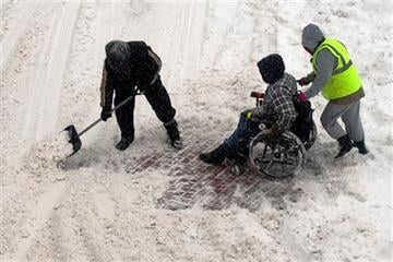 (AP Photo/The Telegram & Gazette, Rick Cinclair). Michael Rae, left, and Olga Clark, right, help a man in a wheelchair through a snow-covered crosswalk on Church Street in downtown Worcester, Mass. Monday Feb. 9, 2015.