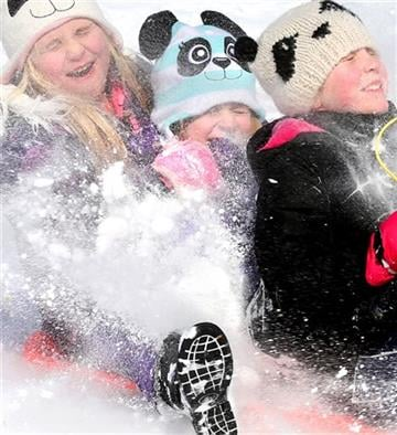 (AP Photo/The Winchester Star, Jeff Taylor). Jamie Treiver, left, Carrie Warner and Camdyn Lockley enjoy a sled ride at Jim Barnett Park, Tuesday, Feb. 17, 2015 in Winchester, Va.
