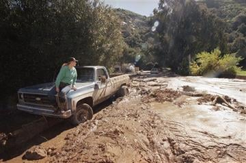 (AP Photo/Nick Ut, File). FILE - In this Feb. 24, 1998 file photo, a woman waits for a tow truck on the hood of her brother's pickup after a wall of mud plowed down Laguna Beach Canyon Road in Orange County, Calif.