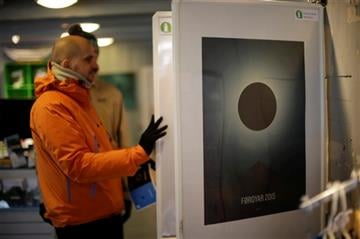 (AP Photo/Matt Dunham). A visitor looks at solar eclipse posters displayed for sale at the tourist office, in Torshavn, the capital city of the Faeroe Islands, Wednesday, March 18, 2015.