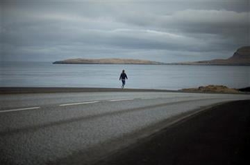 (AP Photo/Matt Dunham). A woman walks along a coastal road in Torshavn, the capital city of the Faeroe Islands, Wednesday, March 18, 2015.