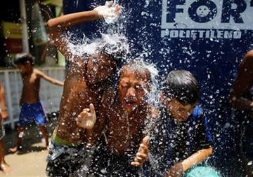 (AP Photo/Leo Correa, File). FILE - In this Jan. 29, 2015 file photo, children play under the water that they manage to spill over from a water tank, to cool off from the summer heat, at the Alemao Complex slum in Rio de Janeiro, Brazil.
