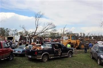 (AP Photo/Regina Garcia Cano). Dozens of people gather to help with cleanup efforts at a farm that was severely damaged by a tornado Sunday, May 10, 2015, in Delmont, S.D.