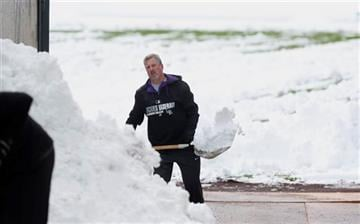 (AP Photo/David Zalubowski). Alan Bossart, visiting clubhouse manager for the Colorado Rockies, shovels snow off the outfield in Coors Field after a wet, heavy snow Sunday, May 10, 2015, in Denver.