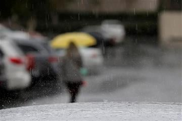 (AP Photo/Jae C. Hong). Rain drops fall on a car parked outside a building, Friday, May 15, 2015, in Buena Park, Calif.