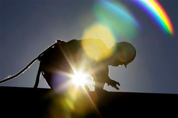 (AP Photo/Gerry Broome, File). FILE - In this July 6, 2010 fik photo, a construction worker is backlit from the morning sun while working on a roof in the heat in Chapel Hill, N.C. as temperatures inched into at least the 90s from Maine to Texas