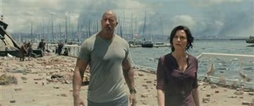 "(Courtesy Warner Bros. Pictures via AP). This photo provided by Warner Bros. Pictures shows Dwayne Johnson, left, as Ray, and Carla Gugino as Emma, in a scene from the action thriller, ""San Andreas."" The movie releases in theaters on May 29, 2015."