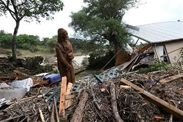 (Jerry Lara/The San Antonio Express-News via AP). A carving of St. Francis of Assisi stands amid debris next to a destroyed home on River Road in Wimberley, Texas, Monday, May 25, 2015.