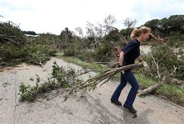 (Jerry Lara/The San Antonio Express-News via AP). Andrea Jones helps remove a downed tree on River Road, Monday, May 25, 2015, in Wimberley, Texas.