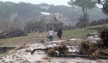 (Rodolfo Gonzalez/Austin American-Statesman via AP). Hudson Doty, 18, left, and Grant Guzal, 17, right, walk along the bank of the Blanco River near the foundation and stilts of the Carey family home on Deer Crossing Lane, in Wimberley, Texas