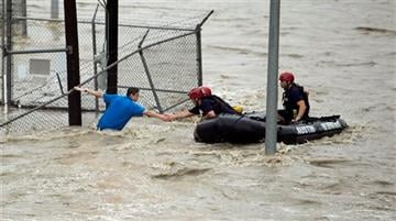 (Alberto Martinez/Austin American-Statesman via AP). Rescue personnel grab the the hand of a man stranded in rushing water at the northwest corner of Lamar Blvd. and 15th St. in Austin, Texas.