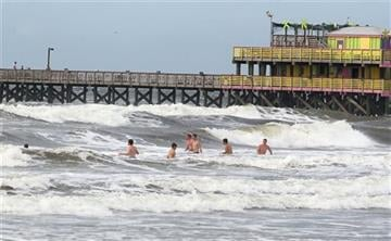 (Jennifer Reynolds/The Galveston County Daily News via AP). Rough surf doesn't deter swimmers near the 61st Street Pier in Galveston, Texas, on Monday, June 15, 2015, as a tropical disturbance approaches the gulf coast.