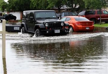 (Gabe Hernandez/Corpus Christi Caller-Times via AP). A vehicle drives through flooded waters caused by a heavy rains Wednesday, June 17, 2015 on Silver Sands Drive in Corpus Christi, Texas.