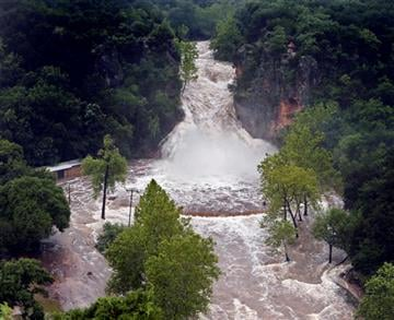 (EDMOND SUN OUT, OKLAHOMA GAZETTE OUT). Water pours over Turner Falls and floods the park below on Thursday, June 18, 2015, in Davis, Okla. Tropical Depression Bill swamped Oklahoma and Arkansas on Thursday...