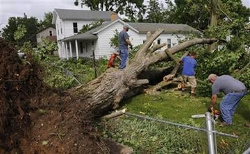 (Rod Sanford/Lansing State Journal via AP). People work together to remove huge fallen trees in Portland, Mich., after severe storms Monday, June 22, 2015.