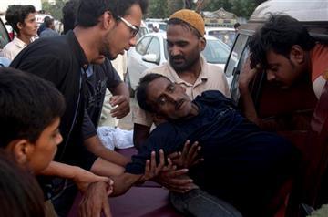 (AP Photo/Shakil Adil). People rush a man to a hospital as he suffers from a heatstroke in Karachi, Pakistan, Tuesday, June 23, 2015.