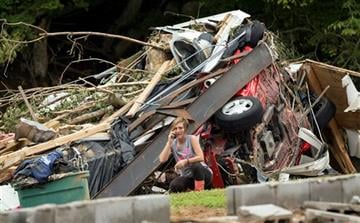 (AP Photo/David Stephenson). Doris Hardin talks on the phone as she takes a break from looking for her missing cats and other belongings from her trailer which was swept away after deadly flooding in Flat Gap, Ky., Tuesday, July 14, 2015.