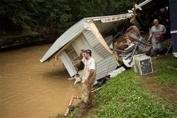 (AP Photo/David Stephenson). Robbie Taylor, left, stares at the swollen creek which destroyed the trailer he shares with his girlfriend Markita Trent, right, after deadly flooding in Flat Gap, Ky., Tuesday, July 14, 2015.