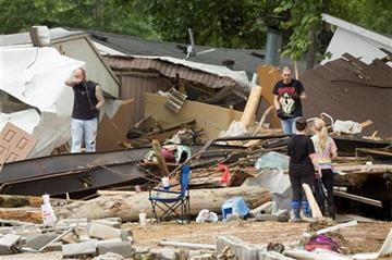 (AP Photo/David Stephenson). Residents of a mobile home park look for belongings after deadly flooding in Flat Gap, Ky., Tuesday, July 14, 2015.