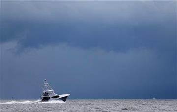 (AP Photo /Wilfredo Lee). FILE - In this Sept. 12, 2014 file photo, a fishing boat heads out to the Atlantic Ocean near Miami as dark clouds loom in the distance.