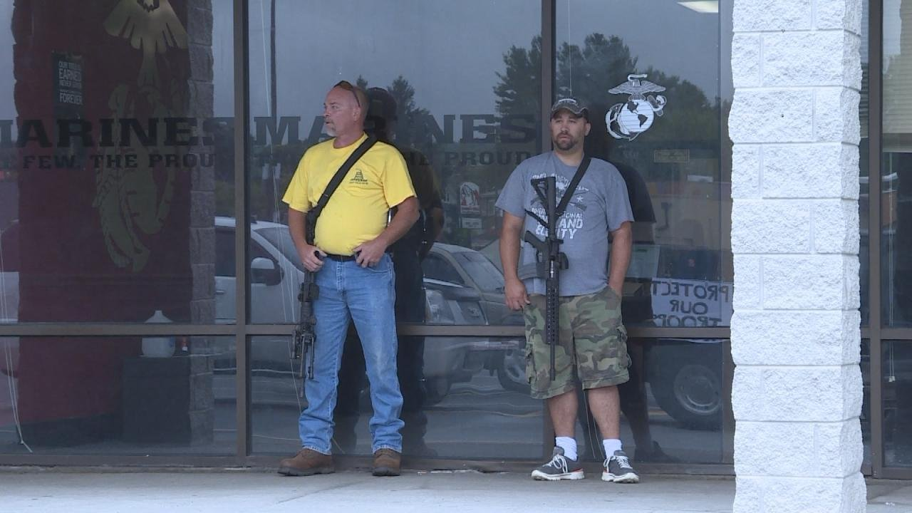 """Two armed men """"stand guard"""" outside a military recruiting center in Princeton, WV on Tuesday."""
