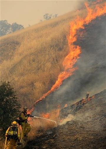 (Kent Porter/The Press Democrat via AP). Firefighters battle a fire burning to the north of U.S. Highway 20 east of Spring Valley in Lake County, Calif., Monday, Aug. 3, 2015.