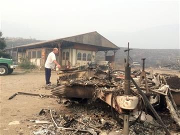 (AP Photo/Brian Skoloff). Steve Surgeon surveys the ruins after he lost everything he owned except his home in a wildfire on the outskirts of Okanogan, Wash., Sunday, Aug. 23, 2015.