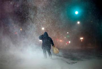 (AP Photo/Robert F. Bukaty). FILE- In a Tuesday, Jan 27, 2015 file photo, a man battles fierce headwinds as he walks on Congress Street in Portland, Maine, during a blizzard.