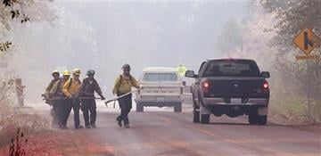 (AP Photo/Elaine Thompson). Firefighters walk through heavy smoke Sunday, Aug. 23, 2015, in Twisp, Wash.