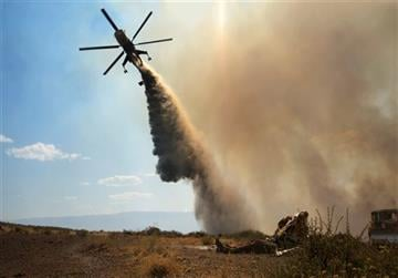 (Eli Peterson via AP). This Aug. 9, 2015 photo taken by Utah state firefighter Eli Peterson shows a firefighter watching as a helicopter makes a water drop over a fire in Owyhee County, Idaho.