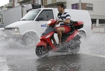 (AP Photo/Lynne Sladky). FILE - In this Sept. 23. 2014 file photo, a motorcyclist negotiates heavily flooded streets as rain falls in Miami Beach, Fla.