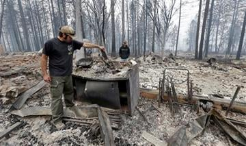 (AP Photo/Elaine Thompson). Adam Bailey, left, looks through the still smoldering remains of his home as his father-in-law Joel Miller looks on Monday, Sept. 14, 2015, in Cobb, Calif.