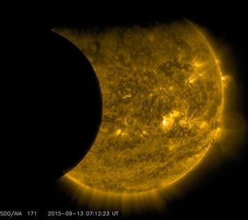 (NASA/SDO via AP). This Sept. 13, 2015 image provided by NASA shows the moon, left, and the Earth, top, transiting the sun together, seen from the Solar Dynamics Observatory.