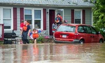 (Daniel Lin/Daily News-Record via AP). Harrisonburg emergency responders help a family evacuate their home as floodwaters block the road in Harrisonburg, Va., on Tuesday, Sept. 29, 2015.