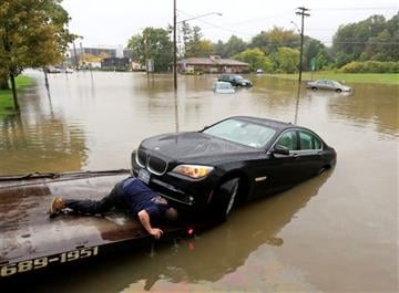 (AP Photo/Mike Groll). A worker prepares to tow a stranded vehicle from a flooded road on Wednesday, Sept. 30, 2015, in Guilderland, N.Y.