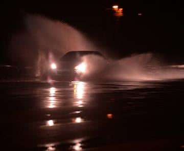 (Tim Kimzey/The Spartanburg Herald-Journal via AP). A car splashes through a puddle as heavy rain falls during the early morning hours, Thursday, Oct. 1, 2015, in Spartanburg, S.C,