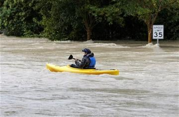 (AP Photo/Chuck Burton). A man paddles a kayak down a flooded street in Columbia, S.C., Sunday, Oct. 4, 2015.