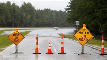 (AP Photo/Mic Smith). signs block entry to U.S. Hwy. 17 North near Georgetown, S.C., Sunday, Oct. 4, 2015 after vehicles became stuck in floodwaters.
