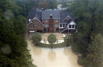 (AP Photo/Chuck Burton). Floodwaters encroach on a large home in Columbia, S.C., Monday, Oct. 5, 2015.