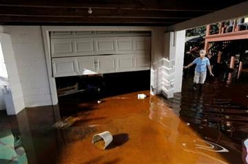 (AP Photo/Mic Smith). Roberta Albers walks around her home after the floodwaters start to recede at French Quarter Creek in Huger, S.C., Wednesday, Oct. 7, 2015.