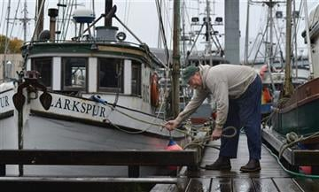(James Poulson/The Daily Sitka Sentinel via AP). Fisherman Sean Cavlan checks the lines on his trawler, Thursday, Oct 8, 2015, in ANB Harbor in Sitka, Alaska.