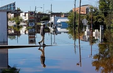 (AP Photo/Mic Smith). Anthony Johnson walks over the floodwaters in downtown Kingstree, S.C., Wednesday, Oct. 7, 2015.