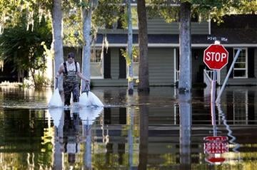 (AP Photo/Mic Smith). Kevin Cox wades through floodwaters by his home on Woodland Dr. in Kingstree, S.C., Wednesday, Oct. 7, 2015.