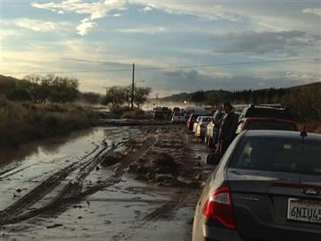(Robert Rocha via AP). In a photo provided by Robert Rocha, cars on a road are stopped because of flooding, with some stuck in the mud in the distance, in Lake Hughes, Calif.