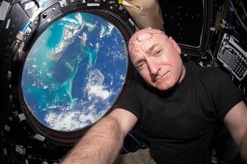 """(Scott Kelly/NASA via AP). This July 12, 2015 photo made available by NASA, astronaut Scott Kelly poses for a selfie photo in the """"Cupola"""" of the International Space Station."""